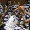 Duke\'s Elizabeth Williams (1) struggles for a rebound against California\'s Gennifer Brandon (25) and Talia Caldwell during the second half of an NCAA college basketball game in Durham, N.C., Sunday, Dec. 2, 2012. Duke won 77-63. (AP Photo/Gerry Broome)