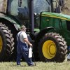 Photo -  A man and two boys approach a farm tractor to get a closer look during the Oklahoma Cooperative Extension Service Whistle-Stop and Festival on Saturday in Wellston. Photo by Jim Beckel, The Oklahoman  <strong>Jim Beckel -   </strong>