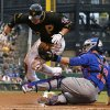 Photo - Chicago Cubs catcher John Baker tags out Pittsburgh Pirates' Clint Barmes who was attempting to score from third during the third inning of a baseball game against the Chicago Cubs in Pittsburgh Thursday, June 12, 2014. (AP Photo/Gene J. Puskar)