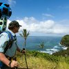 In this undated photo provided by Google, Rob Pacheco, president of Hawaii Forest & Trail, takes in the view at Pololu Valley\'s Awini Trail near Kapaau, Hawaii, while wearing the Street View Trekker. Hawaii\'s volcanoes, rainforests and beaches will soon be visible on Google Street View. The Mountain View, Calif., company said Thursday June 27, 2013 it was lending its backpack cameras to a Hawaii trail guide company to capture panoramic images of Big Island hiking trails. (AP Photo/Google)