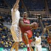 Photo - Texas Tech's Robert Turner, right, drives to the basket as West Virginia's Nathan Adrian defends during the first half of an NCAA college basketball game Wednesday, Jan. 22, 2014, in Morgantown, W.Va. (AP Photo/Andrew Ferguson)