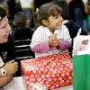 With kindergarten teacher Tina Winkle (left) watching, Itzel Chavez, a kindergarten student at Santa Fe South, reacts as she sees her gift during the annual Christmas Party and gift exchange at Santa Fe South High School in OKlahoma City on Friday, Dec. 3, 2010. Photo by John Clanton, The Oklahoman