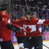 Photo - Canada forward John Tavares, right, and forward Jeff Carter, second from left, celebrate with defenseman Drew Doughty (8) after Doughty scored a sudden death overtime goal against Finland during a men's ice hockey game at the 2014 Winter Olympics, Sunday, Feb. 16, 2014, in Sochi, Russia. Canada won 2-1. (AP Photo/Mark Humphrey)