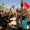 Photo - Shiite tribal fighters raise their weapons and chant slogans against the al-Qaida-inspired Islamic State of Iraq and the Levant (ISIL) in the east Baghdad neighborhood of Kamaliya, Iraq, Sunday, June 15, 2014. Emboldened by a call to arms by the top Shiite cleric, Iranian-backed militias have moved quickly to the center of Iraq's political landscape, spearheading what its Shiite majority sees as a fight for survival against Sunni militants who control of large swaths of territory north of Baghdad. (AP Photo)