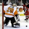 Photo - Philadelphia Flyers goalie Ray Emery (29) deflects a shot as New Jersey Devils right wing Jaromir Jagr (68), of the Czech Republic, watches during the second period of an NHL hockey game, Tuesday, Jan. 7, 2014, in Newark, N.J. (AP Photo/Julio Cortez)