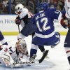 Photo - Tampa Bay Lightning left wing Ryan Malone (12) trips over Washington Capitals goalie Philipp Grubauer (31), of Germany, during the second period of an NHL hockey game Thursday, Jan. 9, 2014, in Tampa, Fla. (AP Photo/Chris O'Meara)