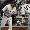 New York Yankees\' Vernon Wells, left, is congratulated by teammate Lyle Overbay after hitting a two-run home run against the Colorado Rockies in the first inning of a baseball game in Denver on Wednesday, May 8, 2013. (AP Photo/David Zalubowski)