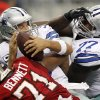 Dallas Cowboys quarterback Tony Romo (9) fumbles the ball while being tackled by Tampa Bay Buccaneers defensive end Michael Bennett (71) as Cowboys\' Tyron Smith (77) tries to hold the line during the second half of an NFL football game, Sunday, Sept. 23, 2012, in Arlington, Texas. (AP Photo/LM Otero)