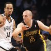 Photo - Los Angeles Lakers point guard Steve Blake (5) drives around Brooklyn Nets point guard Shaun Livingston (14) in the first quarter of an NBA basketball game at the Barclays Center, Wednesday, Nov. 27, 2013, in New York. (AP Photo/John Minchillo)