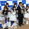 """Photo - FILE - In this May 22, 2013 file photo, Japanese girls pop group AKB48 members and their general producer Yasushi Akimoto, center, pose for photographers during JASRAC (Japanese Society for Rights of Authors, Composers and Publishers) music award in Tokyo. After appointing women and former Olympians to the Tokyo 2020 Olympics board to counter criticism it was dominated by old men, organizers now face a possible new controversy over the appointment of the music producer. The group and its spinoffs are popular not only in Japan, but also other Asian nations and the Japanese government has often appointed them as ambassadors for what it calls """"cool Japan"""" culture. (AP Photo/Shizuo Kambayashi, File)"""