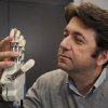 Photo - This undated handout photo provided by Science Translational Medicine shows neuroengineer Silvestro Micera, researcher at EPFL and Scuola Superiore Sant'Anna holding a bionic hand.  To feel what you touch _ that's the holy grail for artificial limbs. In a step toward that goal, European researchers created a robotic hand that let an amputee feel differences between a bottle, a baseball and a mandarin orange.  (AP Photo/Hillary Sanctuary, EPFL, Science Translational Medicine)