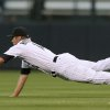 Photo - Colorado Rockies second baseman Josh Rutledge stretches out to catch a pop fly ball off the bat of Milwaukee Brewers' Mark Reynolds to end the top of the fourth inning of a baseball game in Denver on Sunday, June 22, 2014. (AP Photo/David Zalubowski)