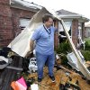 Randy McKeever, removes part of what he believes is his neighbors garage door from the front of his tornado damaged home Wednesday, April 4, 2012, in Forney, Texas. The mayor of Forney, Texas, says it\'s