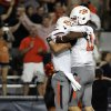 Photo -   Oklahoma States' quarterback Wes Lunt (11) and Tracy Moore (87) celebrate Tracy's touchdown against Arizona during the first half of an NCAA college football game at Arizona Stadium in Tucson, Ariz., Saturday, Sept. 8, 2012. (AP Photo/John Miller)