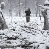 A man stops to photograph the snow-covered Korean War Veterans Memorial in Washington, Monday, Feb. 15, 2016. Bitter cold was replaced by snow, sleet and rain Monday in the mid-Atlantic states and the South, but many residents were able to hunker down at home with federal offices and many businesses closed for Washington\'s Birthday. (AP Photo/Carolyn Kaster)