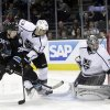 Photo -   Los Angeles Kings goalie Jonathan Quick (32) deflects a shot next to San Jose Sharks center Logan Couture (39) and Kings defenseman Willie Mitchell (33) during the first period of an NHL hockey game Saturday, April 7, 2012 in San Jose, Calif. (AP Photo/Marcio Jose Sanchez)