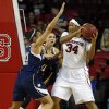 Photo - North Carolina State's Markeisha Gatling (34) keeps the ball from Notre Dame's Natalie Achonwa (11) and Kayla McBride (21) during the second half of an NCAA college basketball game in Raleigh, N.C., Sunday, March 2, 2014. Notre Dame won 84-60. (AP Photo/Karl B DeBlaker)