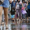 Pedestrians walk during a slight rain brought about by typhoon Melor (local name
