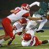 Edmond Santa Fe\'s Trevan Smith tries to get past Lawton\'s Matt Leon, left, Casey Nadeau, and Mike Warren, bottom right, during their high school football game at Wantland Stadium in Edmond, Okla., Thursday, October 11, 2012. Photo by Bryan Terry, The Oklahoman