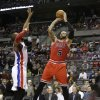 Photo - Chicago Bulls forward Carlos Boozer (5) shoots over Detroit Pistons forward Greg Monroe during the first half of an NBA basketball game in Auburn Hills, Mich., Wednesday, March 5, 2014. (AP Photo/Carlos Osorio)