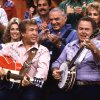 """** ADVANCE FOR WEEKEND EDITIONS, MAY 15-16 ** FILE ** Co-hosts Buck Owens, left, and Roy Clark, right, perform with other cast members during a taping of """"Hee Haw"""" in 1986 in Nashville, Tenn. Time-Life is releasing full """"Hee Haw"""" shows for the first time on VHS and DVD for the 35th anniversary of the show\'s first season. Shown between Owens and Clark is actor Ernest Borgnine, a guest on that episode. (AP Photo/Mark Humphrey)"""