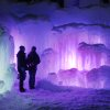 Photo - In this photo taken Wednesday Jan. 8, 2014 patrons tour an ice castle at the base of the Loon Mountain ski resort in Lincoln, N.H. The ice castle begins to grow in the fall when the weather gets below freezing and thousands of icicles are made and harvested then placed around sprinkler heads and sprayed with water.  The castle will continue to grow as long as the temperatures stay below freezing.(AP Photo/Jim Cole)