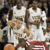 Photo - Virginia Commonwealth University guard Joey Rodriguez (12) and University of Oklahoma guard Willie Warren, bottom right, scramble for the ball as VCU's Larry Sanders, top left, and  Bradford Burgess, top right, look on during the first half of an NCAA college basketball game in Richmond, Va., Saturday, Nov. 21, 2009. (AP Photo/Steve Helber) ORG XMIT: VASH101