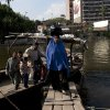 An Egyptian family leaves a ferry boat that is used by residents to cross the Nile river onto the Qursaya island, in Cairo, Egypt, Monday, Jan. 14, 2013. The Egyptian Armed Forces claims that it is the registered owner of the island\'s land, a claim disputed by the some 5,000 farmers and fishermen residents of the embattled island that have been resisting their eviction since 2007. (AP Photo/Nasser Nasser)