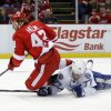 Photo - Tampa Bay Lightning's Victor Hedman (77), of Sweden, trips Detroit Red Wings' Darren Helm (43) after knocking away the puck as Helm skated toward the goal during the second period of an NHL hockey game on Sunday, March 30, 2014, in Detroit. (AP Photo/Duane Burleson)