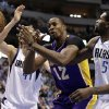 Los Angeles Lakers\' Dwight Howard (12) loses control of the ball fighting for a shot attempt against Dallas Mavericks\' Bernard James (5) and Dirk Nowitzki, left rear, in the first half of an NBA basketball game Sunday, Feb. 24, 2013, in Dallas. (AP Photo/Tony Gutierrez)