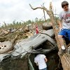 Standing on a fallen tree, Caden Bolles looks over damage to his family\'s home in Little Axe, Oklahoma on Tuesday, May 11, 2010. By John Clanton, The Oklahoman