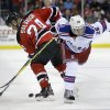 New Jersey Devils\' Bryce Salvador (24) gets tied up with New York Rangers\' Martin St. Louis (26) during the first period of an NHL hockey game game Saturday, March 22, 2014, in Newark, N.J. (AP Photo/Mel Evans)