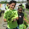 Photo -  A child in the Urban Mission after-school gardening program shows the lettuce she grew in her garden. Photo provided
