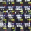 Pedestrians are reflected on an electronic stock board of a securities firm in Tokyo, Thursday, July 17, 2014. Asia\'s major stock markets mostly posted modest gains Thursday after positive U.S. corporate and economic news underpinned confidence. (AP Photo/Eugene Hoshiko)