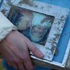 Photo - A woman holds family photos pulled from the rubble at the site of Saturday's fatal mudslide near Oso, Wash., Sunday, March 23, 2014. (AP Photo /The Herald, Genna Martin)