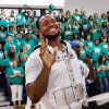 As students and faculty cheer and clap in background, Gerald McCoy flashes a smile and waves to students seated on the other side of the gymnasium after he finished playing the drums. McCoy entered the gym playing a drum with members of the Oklahoma City Thunder drum section. Oklahoma native and professional football player Gerald McCoy spoke to students at his alma mater, Southeast High School, Friday afternoon, May 20, 2011. At the end of his remarks, he announced he is donating some drums to the band and new uniforms for the school\'s marching band, too. Photo by Jim Beckel, The Oklahoman JIM BECKEL