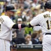 Photo -   Pittsburgh Pirates on-deck batter Casey McGehee (14) greets teammate Neil Walker after Walker scored on a hit by Andrew McCutchen in the first inning of the baseball game against the Houston Astros, Sunday, May 13, 2012, in Pittsburgh. (AP Photo/Keith Srakocic)