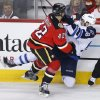 Photo - Winnipeg Jets' Eric O'Dell, right, takes a hit from Calgary Flames' Mark Cundari during second period NHL action in Calgary, Alberta, Friday, April 11, 2014. (AP Photo/The Canadian Press, Larry MacDougal)