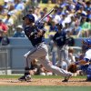 Photo - Milwaukee Brewers' Jonathan Lucroy, left, hits a three run double as Los Angeles Dodgers catcher Drew Butera looks on during the second inning of a baseball game, Sunday, Aug. 17, 2014, in Los Angeles. (AP Photo/Mark J. Terrill)