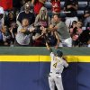 Photo - Oakland Athletics center fielder Coco Crisp (4) jumps up the wall but can't field the two-RBI home run by Atlanta Braves' Phil Gosselin during the sixth inning of a baseball game Friday, Aug. 15, 2014, in Atlanta. (AP Photo/David Tulis)