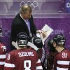 Photo - CORRECTS TO SAY NOLAN IS WATCHING AT LEFT. COACH AT CENTER IS UNIDENTIFIED - Latvia's head coach Ted Nolan, left, listens as an unidentified assistant coach draws up a play during a timeout in the third period of a men's quarterfinal ice hockey game against Canada at the 2014 Winter Olympics, Wednesday, Feb. 19, 2014, in Sochi, Russia. Canada won 2-1. (AP Photo/Mark Humphrey)