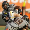 Oklahoma State\'s Lyndell Johnson (27), back, and Brodrick Brown (19) stop West Virginia\'s Connor Arlia (83) during a college football game between Oklahoma State University (OSU) and West Virginia University (WVU) at Boone Pickens Stadium in Stillwater, Okla., Saturday, Nov. 10, 2012. Photo by Nate Billings, The Oklahoman