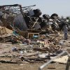 People stand by the remains of a business in Woodward, Okla., Sunday, April 15, 2012. A tornado that killed five people struck Woodward, Okla., shortly after midnight on Sunday, April15, 2012. Photo by Bryan Terry, The Oklahoman