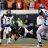 Oklahoma State\'s Charlie Moore (17) dives for a touchdown as TCU\'s Chris Hackett (1), Jason Verrett (2) and Kenny Cain (51) look on during a college football game between Oklahoma State University (OSU) and Texas Christian University (TCU) at Boone Pickens Stadium in Stillwater, Okla., Saturday, Oct. 27, 2012. Photo by Sarah Phipps, The Oklahoman