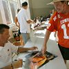 Oklahoma State football coach Mike Gundy signs an autograph for Cowboys fan Gayle Stone, of Woodward, during OSU\'s Fan Appreciation Day on Saturday at Gallagher-Iba Arena in Stillwater. (Photo by John Clanton, The Oklahoman)