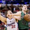 Photo - Los Angeles Clippers forward Blake Griffin, left, battles Boston Celtics center Kelly Olynyk for a loose ball during the first half of an NBA basketball game in Los Angeles, Wednesday, Jan. 8, 2014. (AP Photo/Chris Carlson)