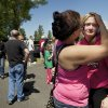 Photo - Briannah Wilson, 21, left, comforts her sister, Trisha Wilson, right, 15, as students are reunited with family at a shopping center parking lot in Wood Village, Ore.,  after a shooting at Reynolds High School Tuesday, June 10, 2014, in nearby Troutdale. A gunman killed a student at the high school east of Portland Tuesday and the shooter is also dead, police said. (AP Photo/Troy Wayrynen)