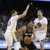 Photo - San Antonio Spurs guard Tony Parker drives to the basket between Golden State Warriors guard Stephen Curry, left, and forward David Lee during the first quarter of an NBA basketball game Saturday, March 22, 2014, in Oakland, Calif. (AP Photo/Eric Risberg)