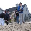 Volunteers shovel sand from the front yard of a home near the ocean in Lavallette, N.J. Friday, Jan. 4, 2013, shortly before Congress voted to approve aid for victims of Superstorm Sandy. Many shore residents were angry that Congress took so long to act after the Oct. 29 storm. (AP Photo/Wayne Parry)