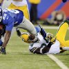New York Giants\' David Wilson (22) is tackled by Green Bay Packers\' Jarrett Bush during the first half of an NFL football game, Sunday, Nov. 25, 2012, in East Rutherford, N.J. (AP Photo/Bill Kostroun)